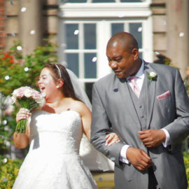 Bride and groom laughing under confetti